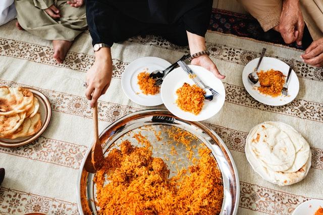 Ľudia sediaci na zemi okolo spoločného jedla počas sviatku