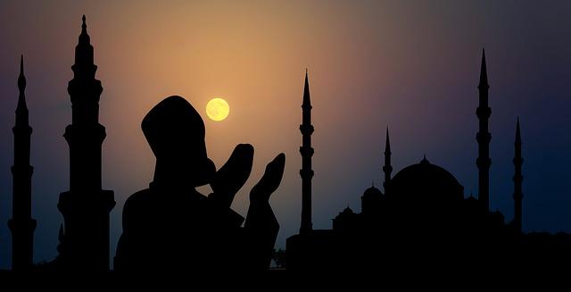 Silueta modliacej sa osoby počas západu slnka pri siluetách veží