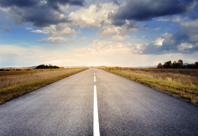 Asfaltová cesta uprostred prírody, modrá obloha a oblaky