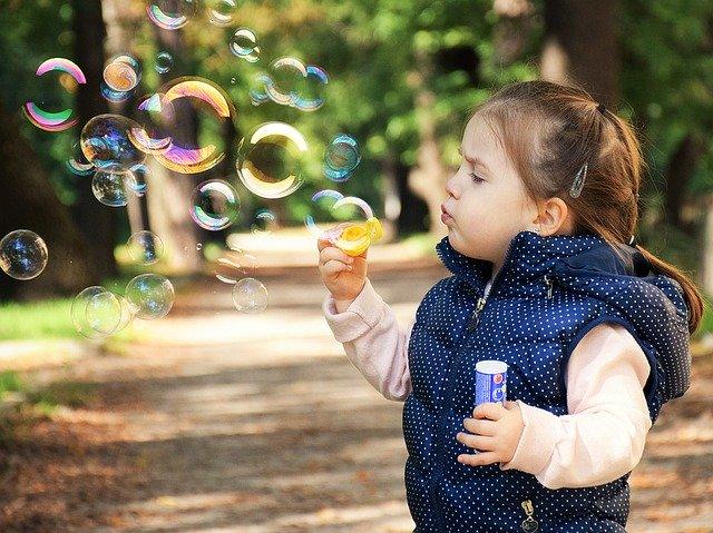 Malé dievča v parku robí bubliny