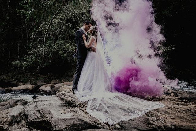 Ženích a nevesta stoja na skale, bozkávajú sa a za nimi je kúdol ružového dymu.jpg