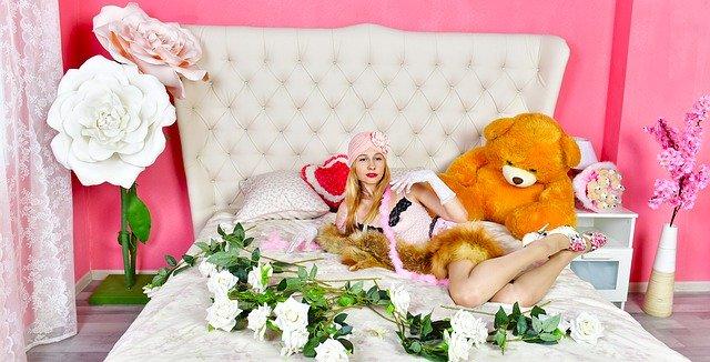 Žena v erotickej spodnej bielizni leží na ružovej posteli, pri nej sú ruže a plyšový medveď.jpg