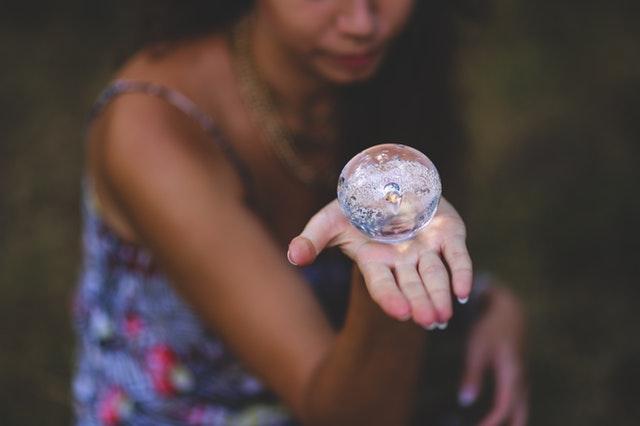 Žena vo farebných šatách drží v ruke sklenené guľu.jpg